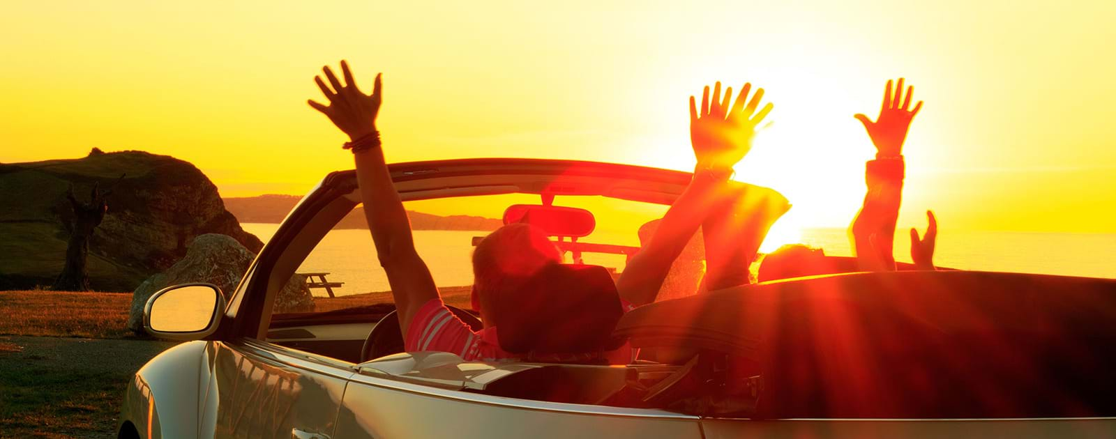 Group riding in convertible hands in the air
